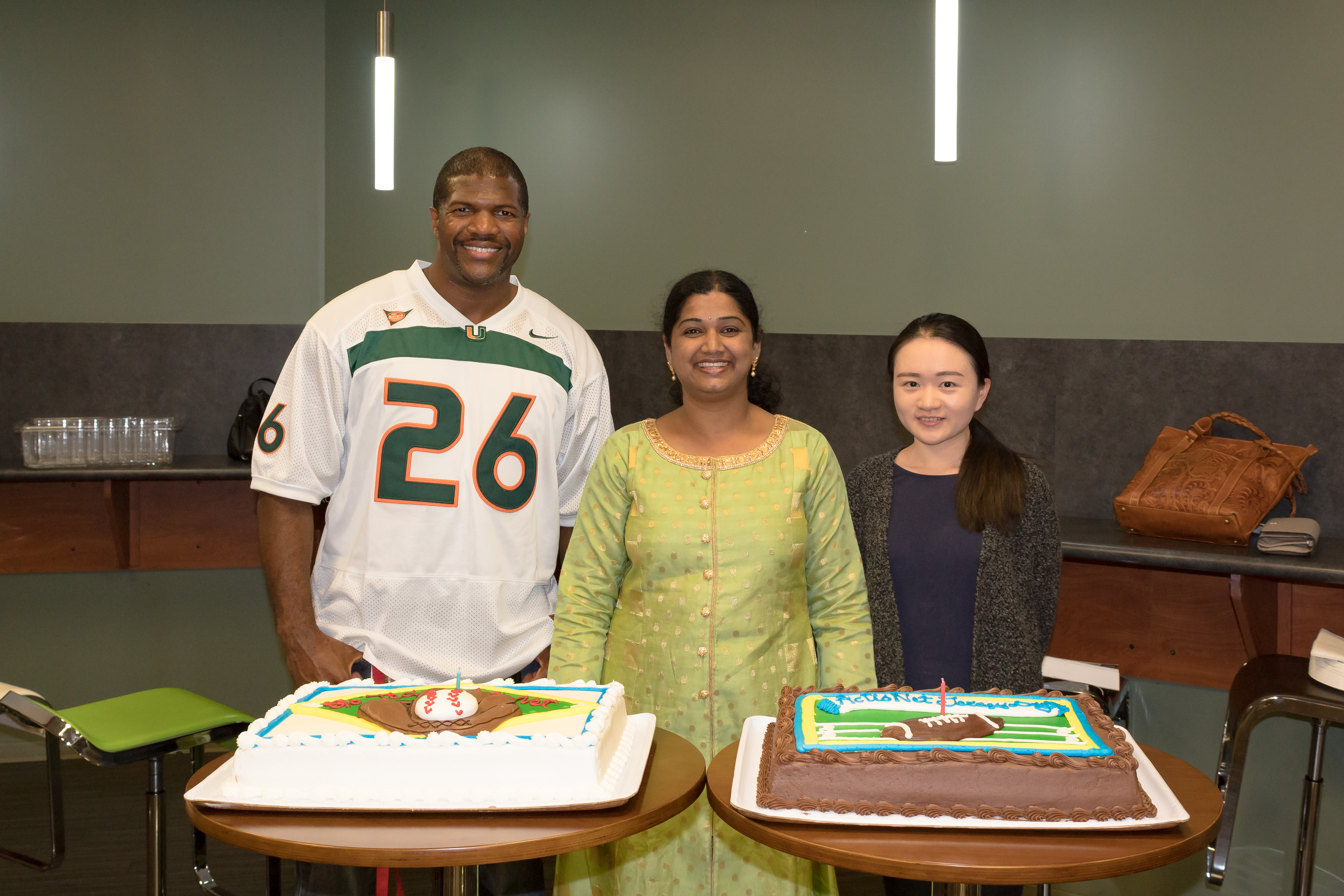 ActioNeters with September birthdays pose for a photo with the sports-themed cakes