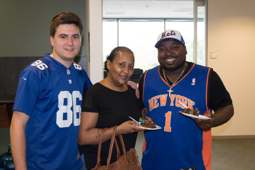 ActioNeters eat cake together at Wear Your Favorite Team Jersey Day