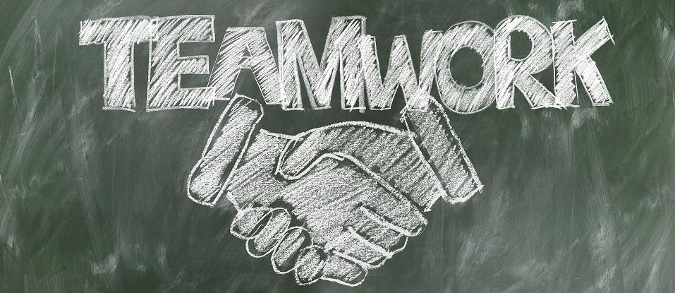 Chalkboard with teamwork written on it overtop of shaking hands