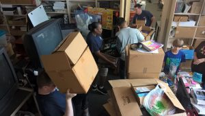 Volunteers moving and organizing boxes at Capital Heights Middle School
