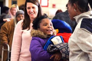 Kids accept coats from ActioNeters