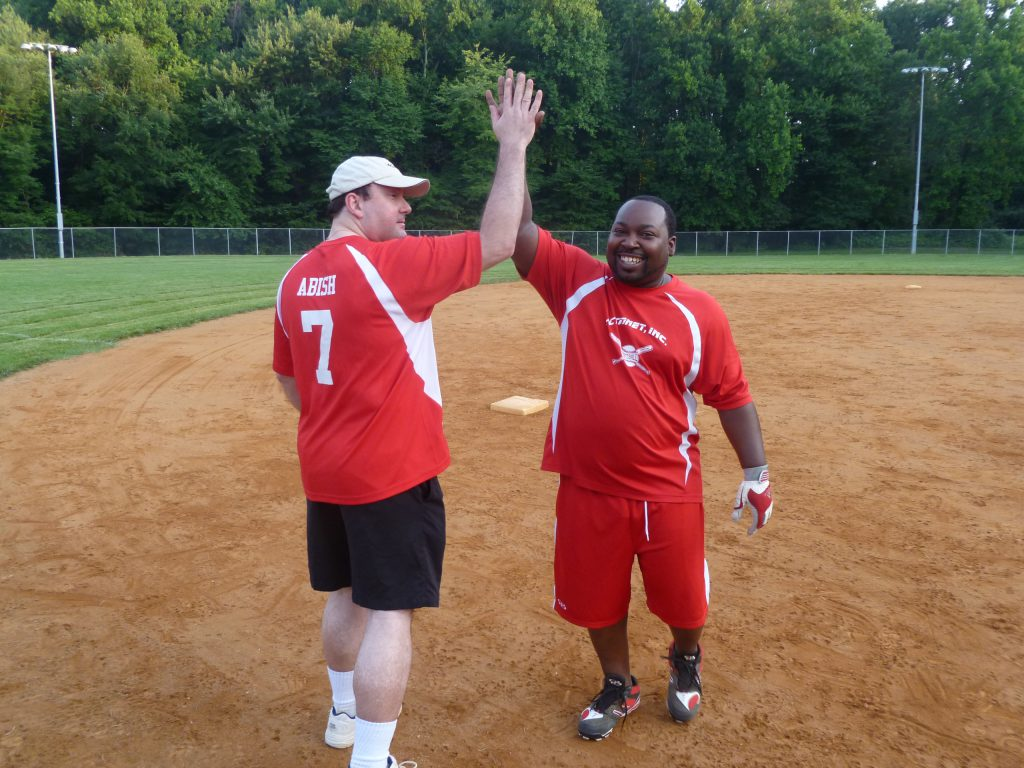 ActioNeters Jeff A. and Tyreace R. High Five on the Softball Field to Celebrate Great Teamwork