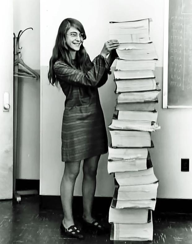 Margaret Hamilton, Apollo 11 director of software engineering, standing next to a stack of code