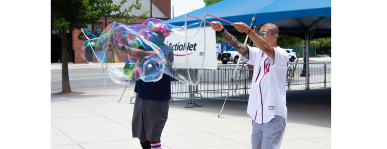 ActioNeters Bobby and Tony Create Giant Bubbles to Welcome Attendees to the ActioNet HQ Summer Picnic
