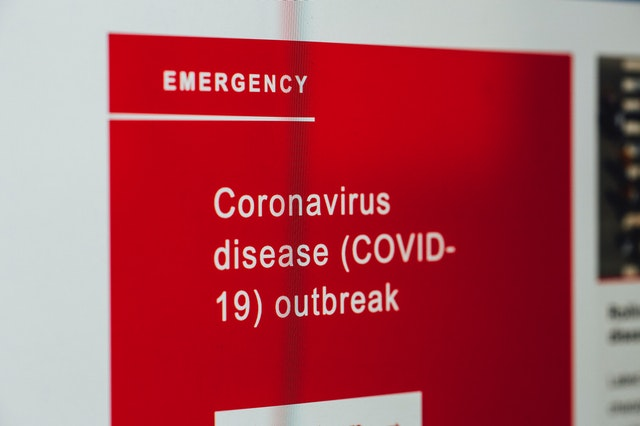 "A photograph of a sign reading 'Emergency Coronavirus disease (COVID-19) outbreak"""
