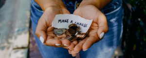 """A person holding change with a sign reading """"make a change"""""""